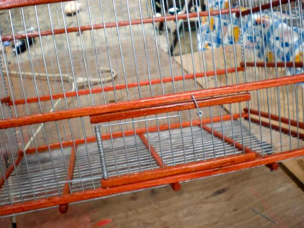 luego bajamos, con ayuda de la pinza, el alambre que habiamos retirado parcialmente tratando de unir el resorte y la puerta a la jaula.
